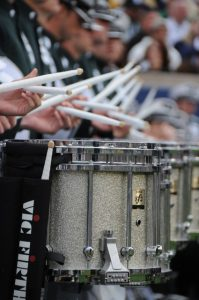 Drumsticks playing marching snare drums.