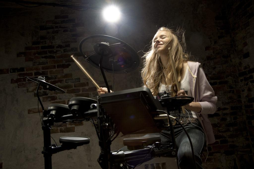 Teenage girl playing electronic drum kit.