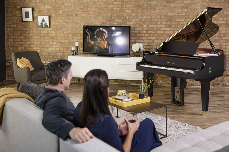 Couple on a couch in a living room watching a self-playing grand piano play.