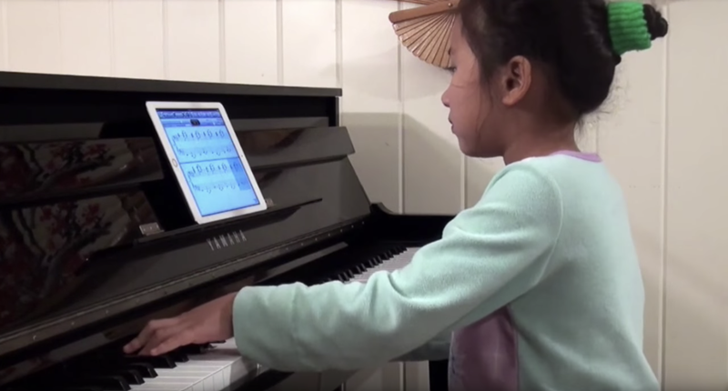 Young girl using sheet music on a tablet to play on an upright piano.