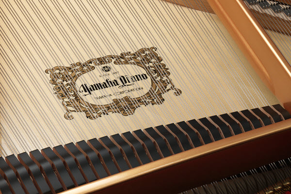 """Closeup of strings inside a piano with a logo underneath that indicate """"Yamaha Piano."""""""
