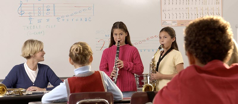 Young students playing woodwinds with a teacher coaching.