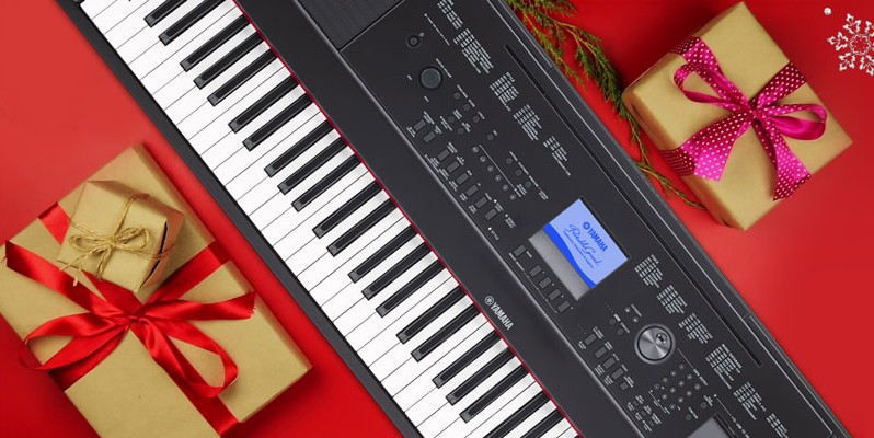 Yamaha keyboard on a flat surface wrapped in holiday paper.