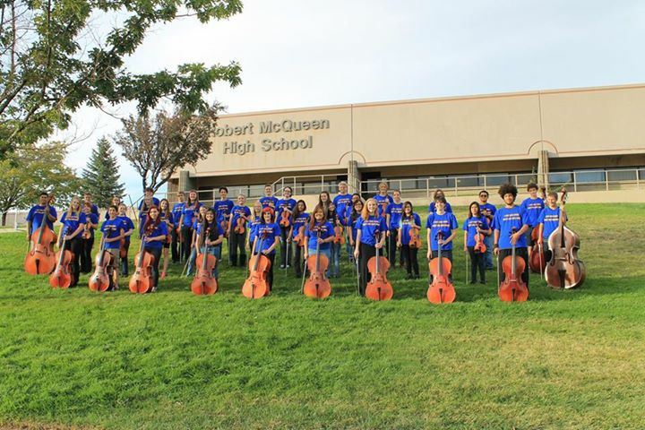 High school students standing in three rows wearing matching t-shirts and jeans on the lawn in front of their high school. Each student is holding their instrument, a violin, viola, cello or upright bass in front of them.