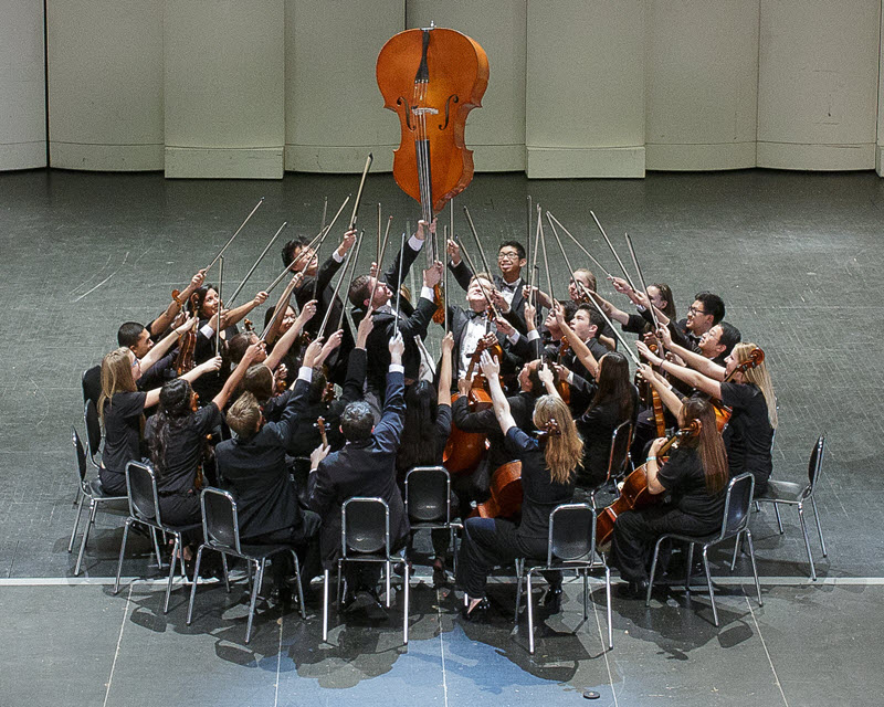 The McQueen High School Orchestra's young musicians in a playful photo showing them on a stage with their chairs pulled together into a tight circle facing inward with an upright bass raised in the center upside down and the players with their bows pointing towards it.
