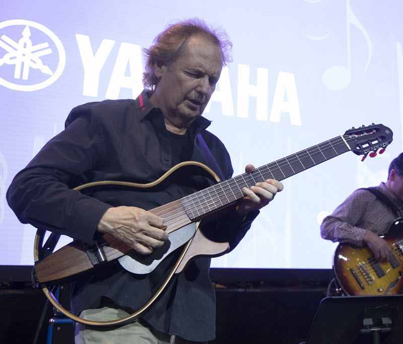 Lee Ritenour playing his nylon-string Silent Guitar on stage with another guitarist playing an electric guitar in the background while standing in front of a projection of the Yamaha logo.