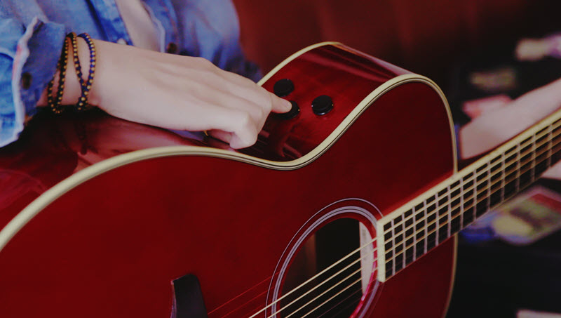 Woman's hand resting on the side of the body of an acoustic guitar pointing to three little plastic knobs on the side of the guitar..