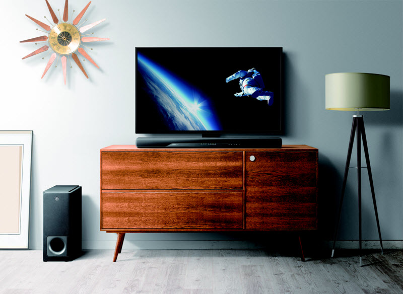 Entertainment area of a living room setup with a sun shaped clock on wall, a wood credenza with a flat screen TV and sound bar on top and a subwoofer and a floor lamp on rug on floor.