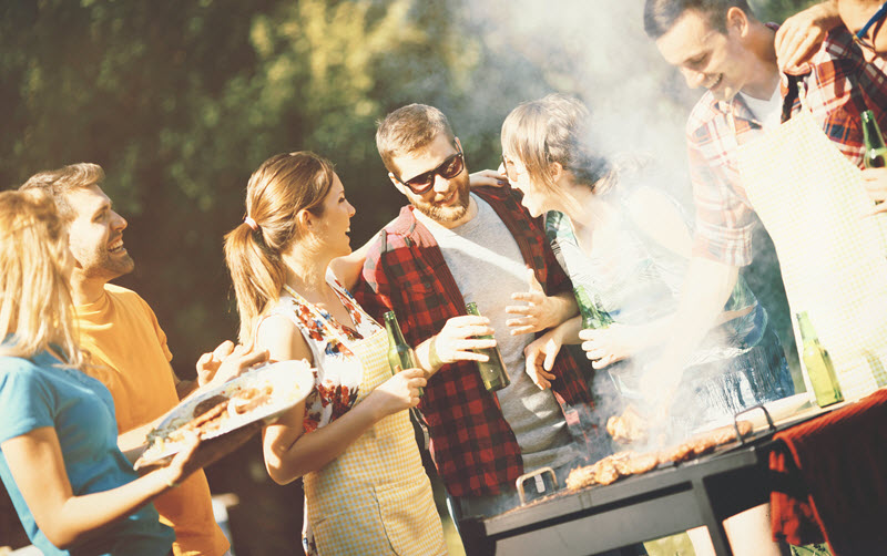 Group of men and women laughing and holding plates of food next to a grill in a backyard.