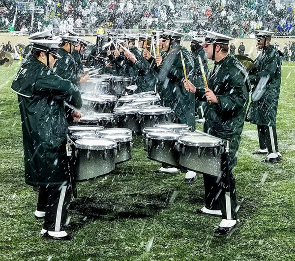 Marching band's drumline lined up playing drums on field while it is raining heavily.