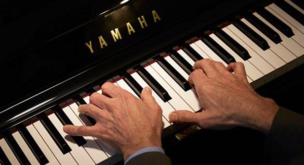 Man's hands on a Yamaha piano keyboard.