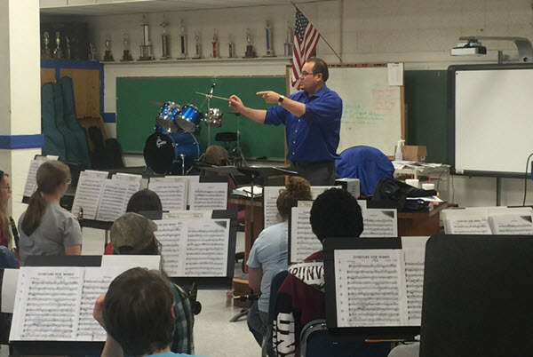 Male teacher conducting a school band class of teenagers.
