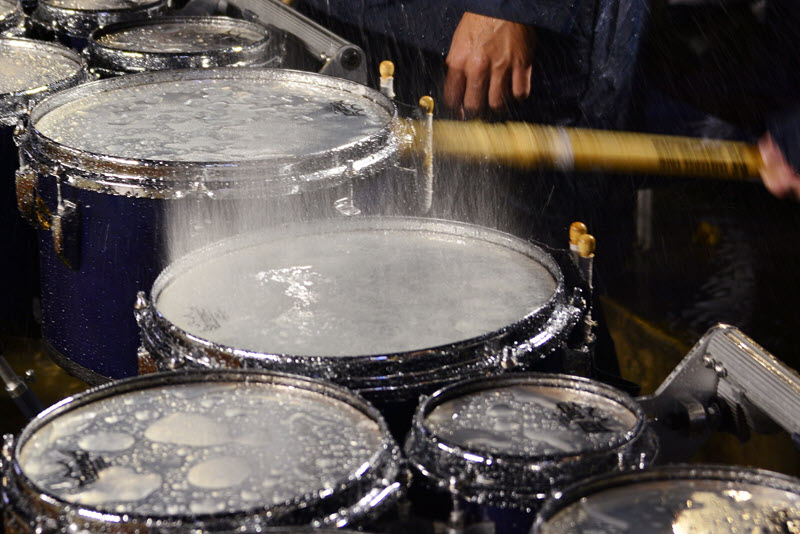 Snare drum heads being struck by drumstick while in pouring rain.