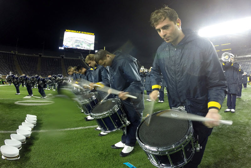 Marching band's drumline marching and playing on a field while rain falls heavily.