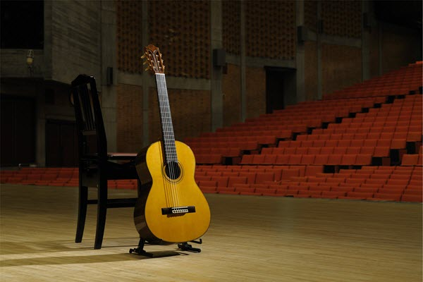Classical guitar upright on a stand next to an empty wooden chair center stage in a large empty concert hall.