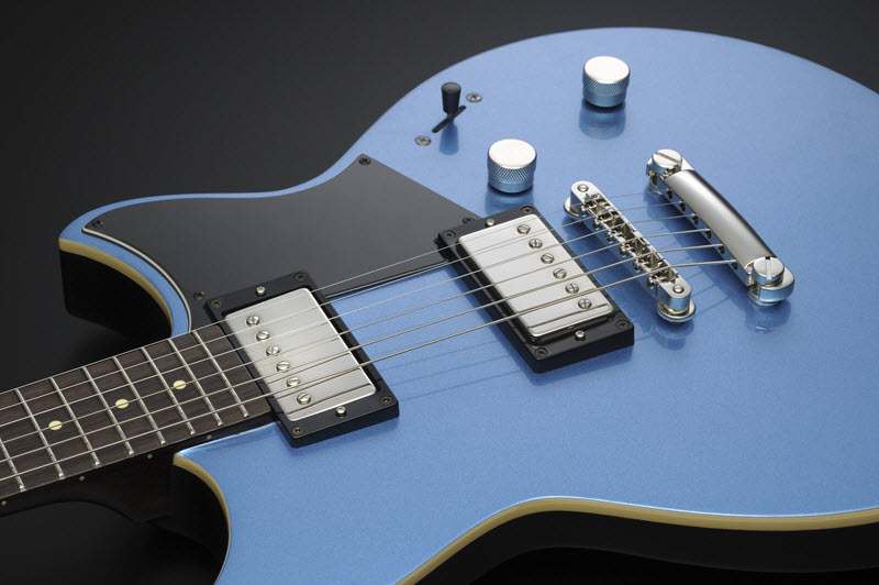 Body of a blue and silver color electric guitar laying face-up showing the pickups clearly.