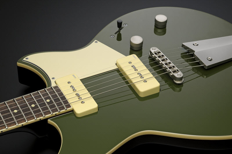 Body of a green and yellow electric guitar lying face-up to show the pickups.