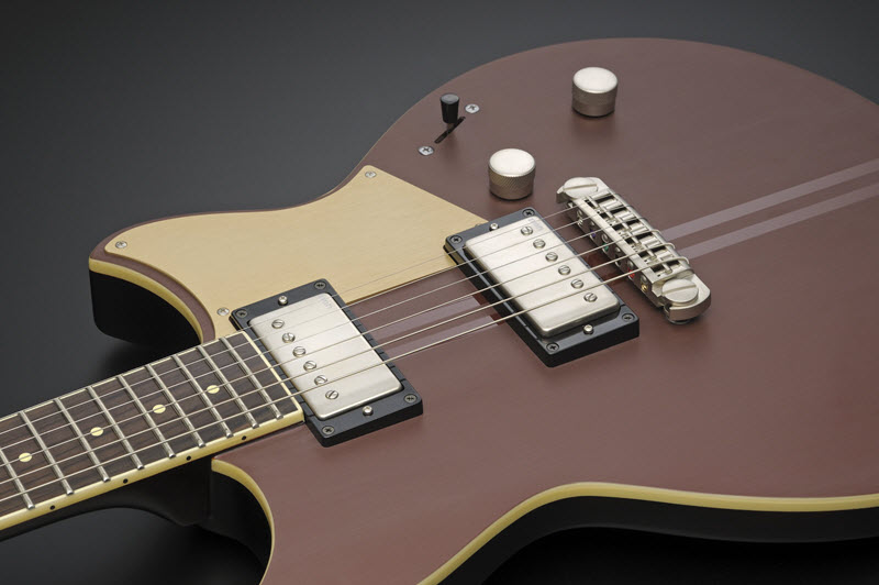 Body of a brown and beige electric guitar lying face-up to show it's pickups.