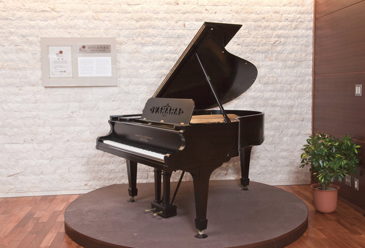 An antique grand piano on a small elevated circle display.