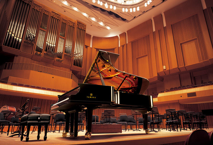 A grand piano alone on a stage in a concert hall.