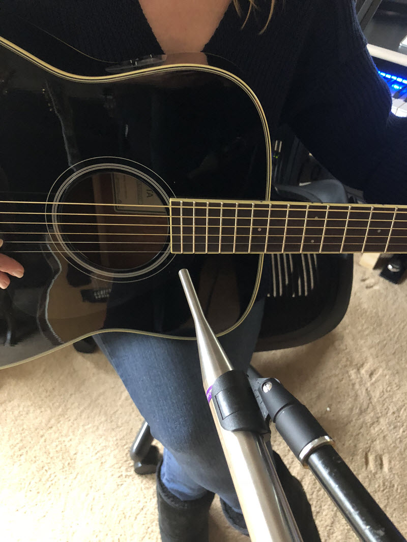 Someone holding a guitar ready to play with a microphone positioned at base of neck where meets the hole on frot of guitar.