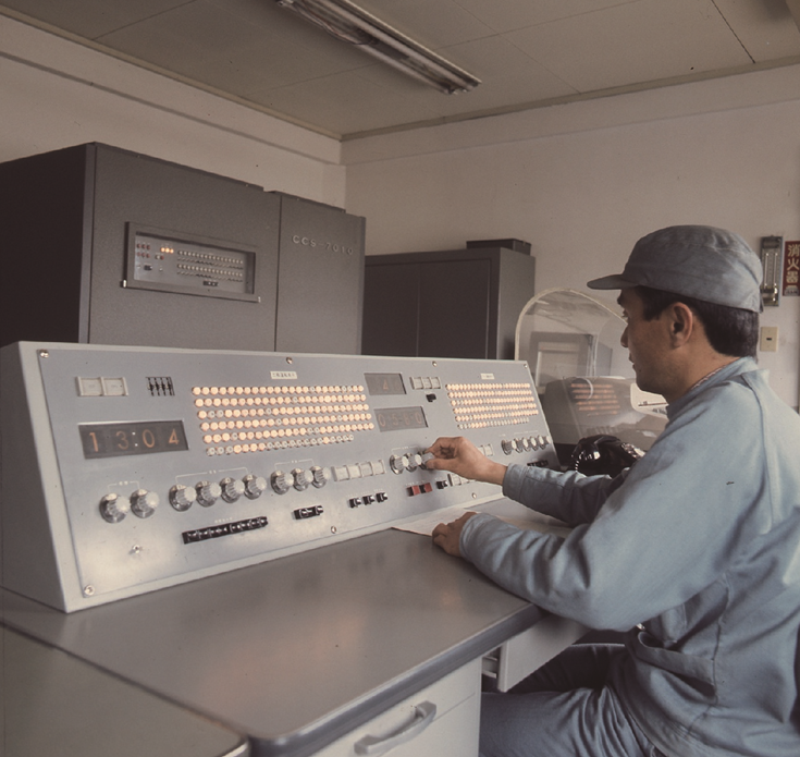 Man in scrub coat with hard hat sitting at an older computer panel.