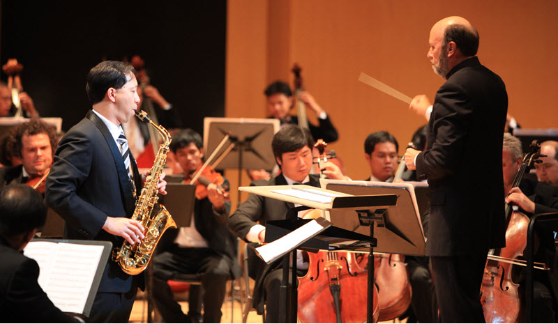 Orchestra on stage performing with conductor and featured saxophone playing in the foreground.