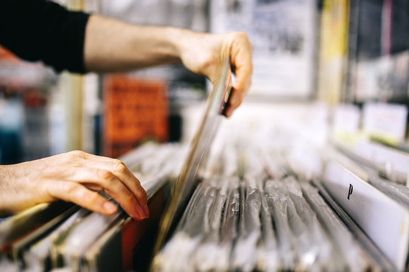 A man's hands as he selects a particular album out of a record store bin of albums.