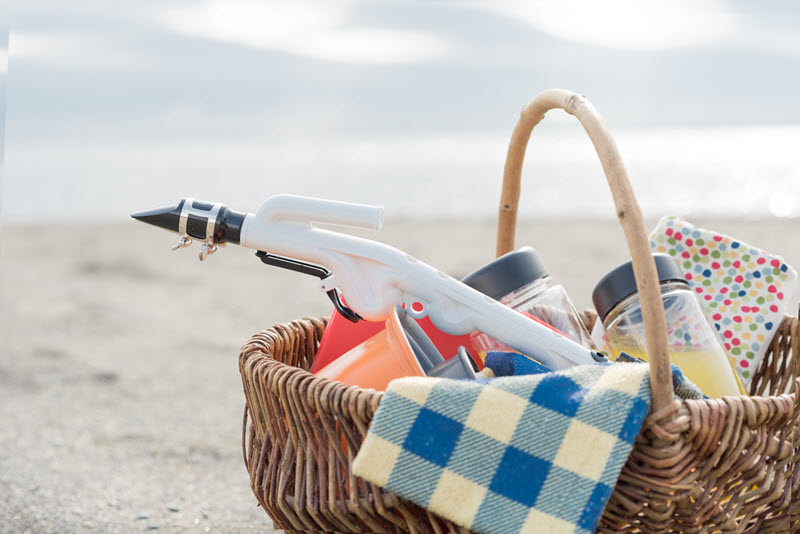 Picnic basket on sand on the beach with various jars and tablecloth and a plastic reeded instrument sticking out of the top of the basket.