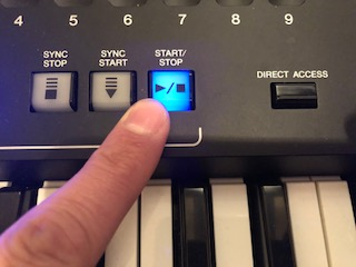 Finger pressing button on electronic keyboard panel.