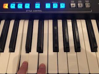 Two fingers playing electronic keyboard with lit up buttons on panel above.