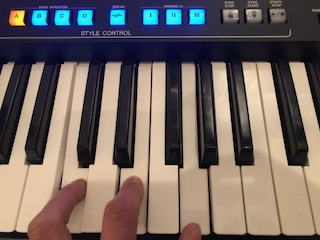 Hand playing electronic keyboard with buttons lit up on panel above.