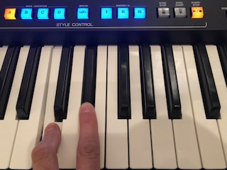Hand playing an electronic keyboard with panel buttons lit up above.