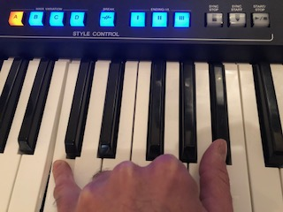 Hand playing electronic keyboard with buttons on panel lit above.