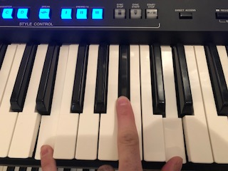 Hand playing electronic keyboard with buttons on panel above lit.