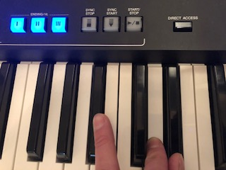 Hand playing electronic keyboard with some of the buttons on panel above lit.
