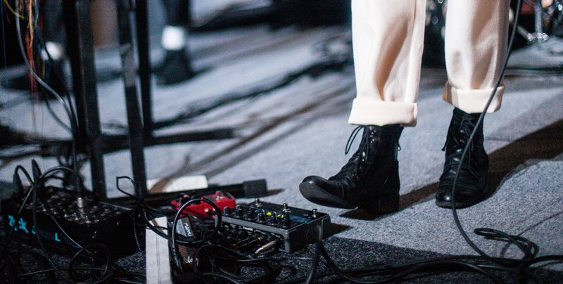 Shot of someone's lower legs in twills and boots using the effects pedals for guitar.