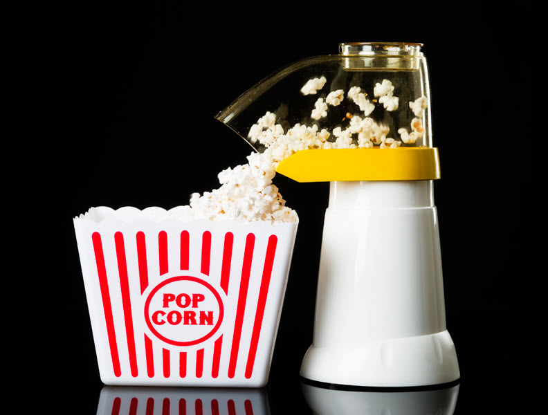 Air popper popping popcorn and it falling into a serving container.
