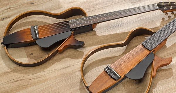 Two electric guitars with open bodies laying on a table.
