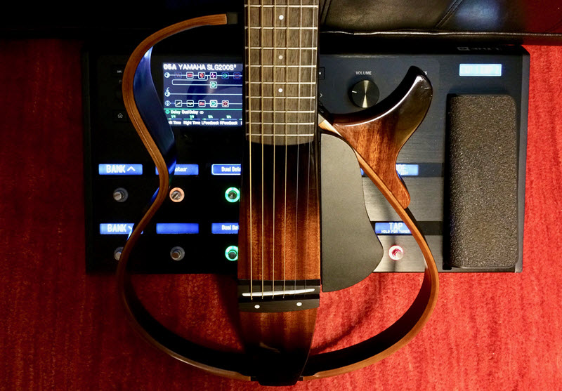 "Open bodied electric guitar on its end in front of a control panel with buttons and knobs and a display screen with word ""Yamaha SLG2008"" visible."