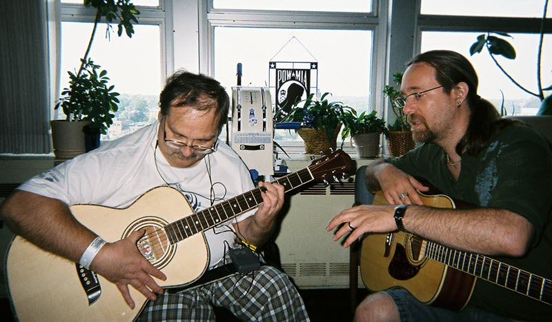 Two men seated with acoustic guitars.