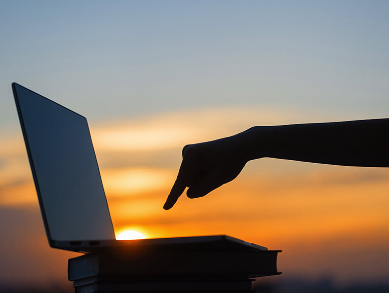 Hand poised with finger extended above a laptop keyboard ready to press a key with the sun going down in background.