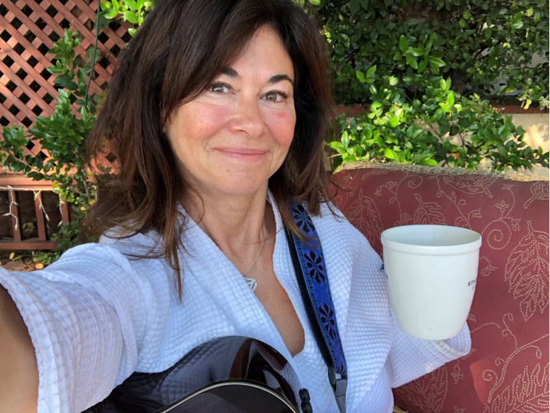 Woman sitting on a deck with a cup of coffee and her guitar.