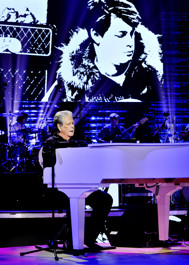 Brian Wilson playing a grand piano.