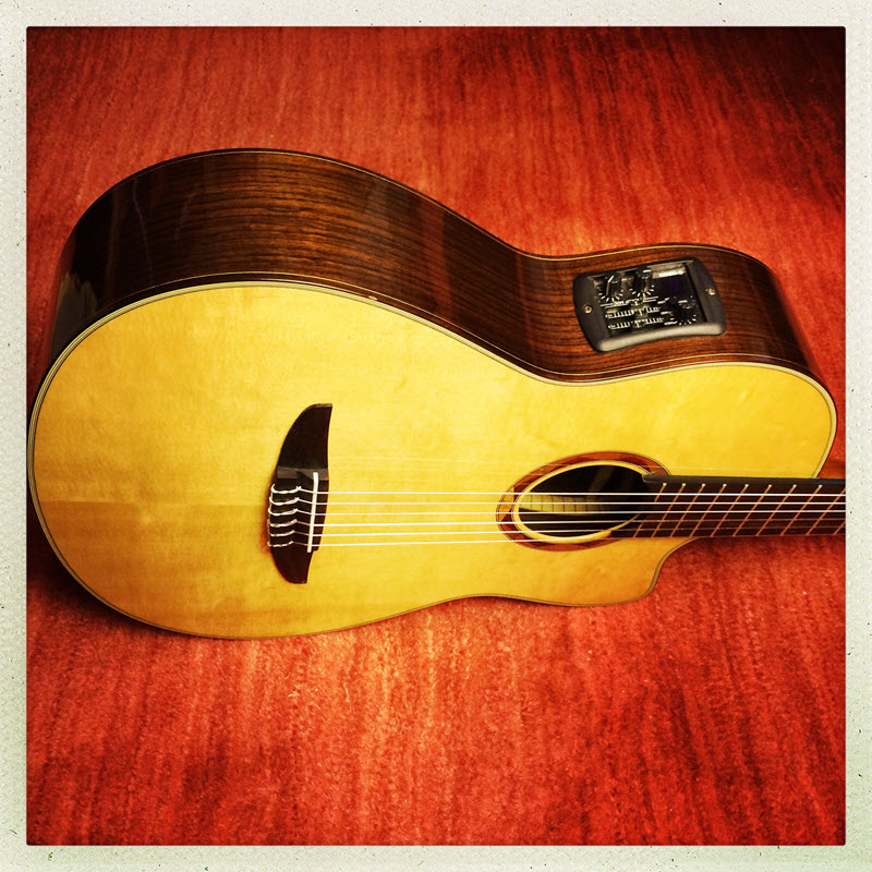 Acoustic Guitar laying on its side on a wood surface.