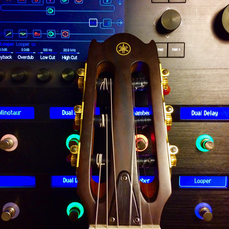 Guitar head leaning against a control panel.