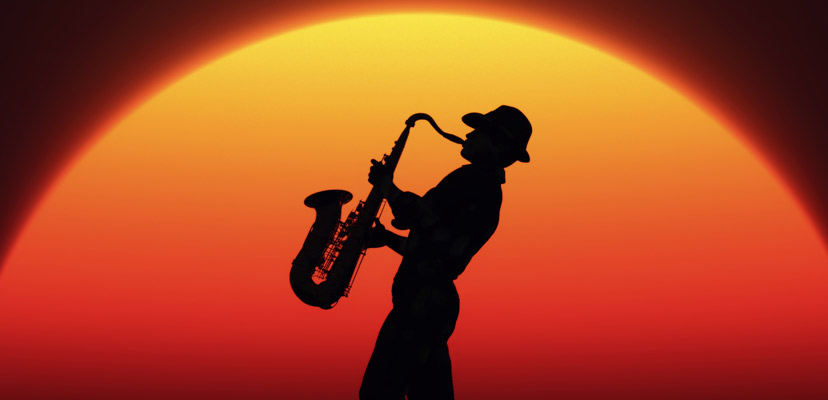 Sunset behind the profile of a man playing a saxophone.