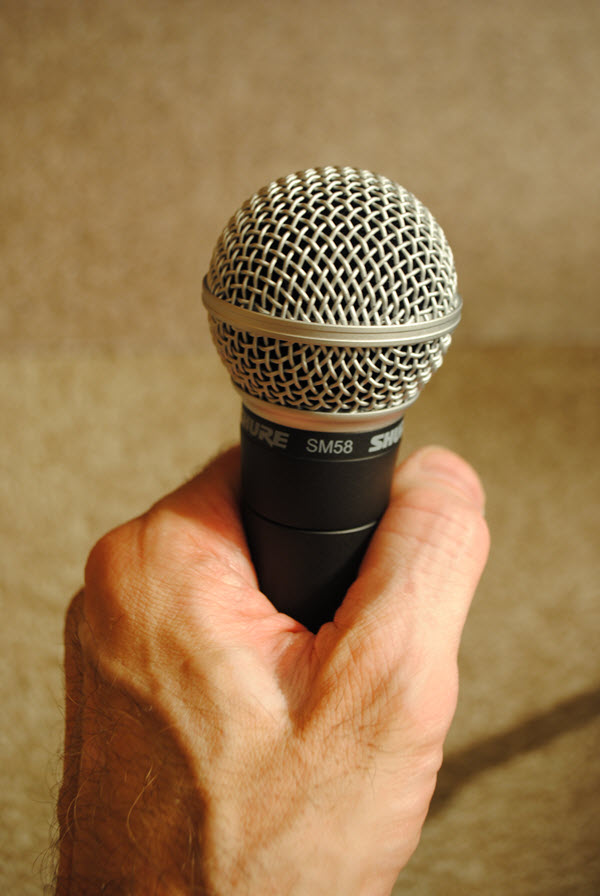 Hand holding microphone.