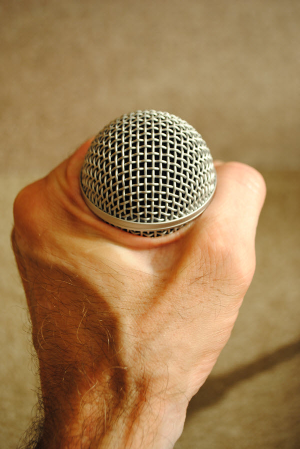 Hand holding a microphone and hand is gripping grill.
