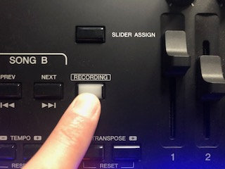 Finger pressing recording button.
